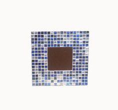 Espejo artesanal. Hecho a mano con mosaico de la colección ARABIA, serie MIX BLUE&SILVER. Formado por teselas de vidrio reciclado con fondo azul y plateado. Ideal para colgar en la pared aportando un aire juvenil y veraniego. Acabado en terciopelo azul marino.