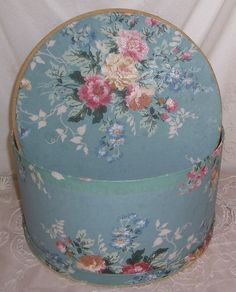 Charming antique hat box dating to the 1920s/40s. It is made from heavy cardboard and covered in beautiful vintage wallpaper that has a blue background patterned with pink cabbage roses and flowers.