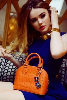 orange bag with cobalt blue dress