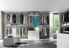 Sleek walk in closet with gray carpet