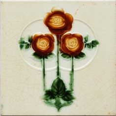 A cream ground low relief tile with a triple rose, stem, and leaf design in dark caramel and green. Condition:...