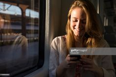 View top-quality stock photos of Smiling Young Woman On A Train Looking At Cell Phone. Find premium, high-resolution stock photography at Getty Images. Phone Photography, Meeting New People, Still Image, Young Women, Smile, Stock Photos, Train Station, November, Photoshoot