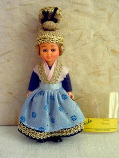 This little doll wears the typical costume of the German town of Passau, in Bavaria. She is garbed in a blue costume consisting of a dark blue brocade skirt under a light blue brocade aprons with a flower design, a dark blue felt top under a pink satin and golden lace shawl. On her head is the Passau Golden Cap, a traditional headdress worn by town women and designed to show off the wealth of their family. The cap is derived from a similar one more common in Austria, and is heavily ...