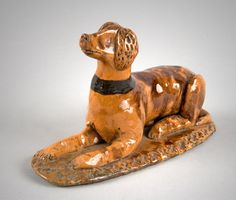 Molded and slab redware recumbent dog; base decorated with band of impressed crosses conforming to the perimeter. Decorated manganese slip on orangey body. Repair to neck and base. (Height: 3.25 inches; length: 6.125 inches; width: 2.5 inches.)