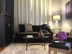 A black velvet sofa, a stunning rug and luxurious drapes combine to tell a visual story in this boutique hotel living room. The ensemble, with chic, rich textures and purple accents, creates an intimate, global feel that escorts visitors into European elegance with a cozy first impression.