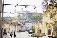Bratislava street and church with castle in the background and tram lines by Shiny Thoughts in 'Bright and Bold in Bratislava' #Bratislava