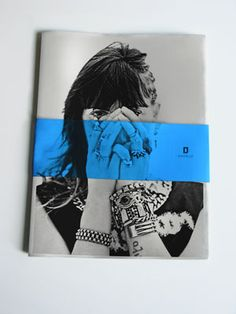 Not only a a creative treatment of color, but as well as material and physical presentation. The blue band around the publication attracts viewers, and adds character.