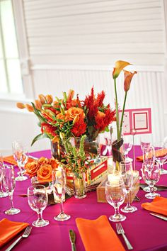 A vibrant hot pink and orange tablescape with floral centerpiece by Petalworks.