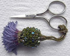 "Thistle Scissor Fob by Sylvia Fairhurst: ""constructed in two parts, the first being a flat base with fringing, the second is the body of the thistle. The two are then joined together, the strap is a continuation of stitching from the body."" (Class info.)"