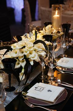 The low centerpiece of white calla lilies and black feathers looks so chic on this black lacquered reception table.