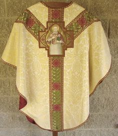 Gold/White fabric with green/red galloon.  Nice size and shape applique.  Attractive vestment