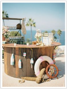 A wood bar with a lifesaver, ship wheel and nautical props for cocktail hour :: A pastel preppy nautical seaside La Jolla Wedding with flower power inspirations a la daisies, kitschy Gilligan's Island tones and vintage life savers and nautical treasures :: Pastel Nautical La Jolla Wedding by Alchemy Fine Events www.alchemyfineee... | Wedding Dress Watters | Wedding Shoes Jimmy Choo | Photos Ashley Kelemen | Flowers by Krista Jon