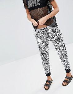 Pantalones de chándal ajustados con puños y estampado integral de palmeras Rally de Nike