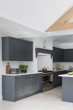 Create a dark grey shaker kitchen with white worktops to create a dark contemporary kitchen. Add classic details like a kitchen mantle to create a cosy kitchen. Masterclass kitchens are available across England, Wales, Scotland and the Channel Islands Modern Shaker Kitchen, Shaker Style Kitchen Cabinets, Dark Grey Kitchen Cabinets, Cosy Kitchen, Grey Kitchen Island, Open Plan Kitchen Living Room, Kitchen Dining Living, Kitchen Mantle, White Kitchen Worktop