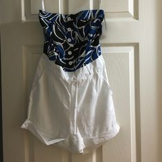 White shorts romper with floral print top Romper, shorts are white (look like linen) attached top silky floral print. 100% polyester. New with tags, never worn. Floral top colors include white, black, and blue. Comes with belt buckles, no belt included. Elastic around waist. Extra button included. Peppe peluso Pants Jumpsuits & Rompers