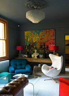 (Farrow & Ball's Downpipe) walls and ceiling. the white Egg chair by Arne Jacobsen, conranshop.co.uk, vintage finds (such as the blue chair and gold table), and high-street bargains (the table lamps and pouffes, all homesense.com).  Chandelier is from the frenchhouse.co.uk