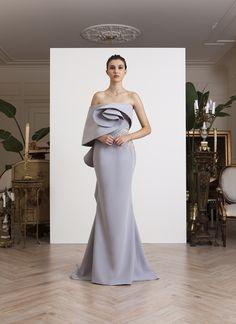 Off-shoulder, one shoulder, light gray crepe gown, with asymmetrical sculptural volume on bust and back, embellished with gold and silver goldwork
