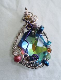 Wire-wrapped glass pendant with crystals and freshwater pearls.
