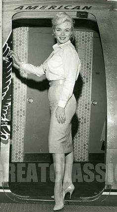 Marilyn Monroe in a pencil skirt and button up top boarding a plane