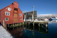 Polar Museum in Tromso Norway reflects into still waters of a finger of the Norwegian Sea