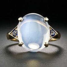 Un anillo contemporánea preciosa fijó con una piedra de luna que brilla intensamente luminosa con un brillo de zafiro azul en cada lado. Las medidas de piedra de la luna apenas por debajo de 1/2 de pulgada de largo y 3/8 pulgada de ancho