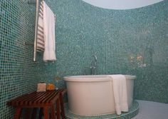 Glass mosaic tiles have a wonderful reflective quality and when done in shades of blue and green, they really look like water. You are literally surrounded by them here. The tub rests on a glass pedestal, making it feel even more special.