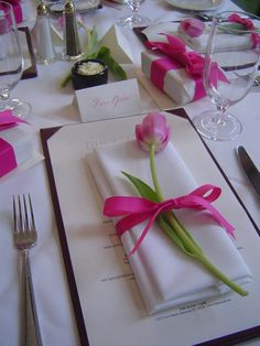 Tulip with Napkin — If you'd rather add a real tulip to your napkin fold, check out this idea from At Home With The Waldreps. No instructions are given, but they're not actually needed. These lovely pink tulips adorned a bridesmaids' table. What a simple way to add color and class to a tablescape. #napkinfold #tulip