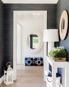 White and black foyer features walls clad in black grasscloth lined with a white console table and a round rope mirror.