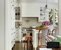 The kitchen was custom-designed featuring classic white cabinets and carrara marble countertops along with Halophane Pendants from Urban Archaeology and some charming French Bistro Stools.