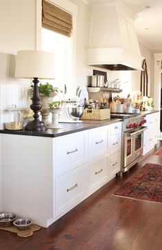 Black and white kitchens. wood Floors, white recessed cabinets and black granite