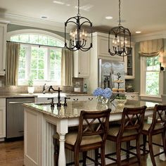 Traditional Kitchen Design iron chandeliers, wood barstools and white cabinets and large kitchen island Driggs Design