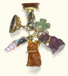 COLLECTION OF SIX CHARMS, EARLY 19TH CENTURY AND LATER Comprising: an early 19th century gold and hardstone intaglio seal, depicting the profile of a Roman emperor, a carnelian seal with silver and gold falcon surmount, a charm in the form of an enamel slipper concealing a silver mouse, a green enamel four leaf clover and a purple glass pug and orange glass cat charm.