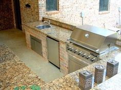 Small custom built outdoor kitchen with granite countertop and built in gas grill