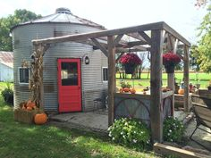 We bought this bin last year from a farmer and dismantled it ourselves in 8 hours and brought it home. Ed reassembled it this spring and used beams from the barn we had to tear down to make the pergola. The old door was here when we moved in and I just painted it red. We love it!