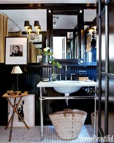 """""""This little black lacquered box of a guest bath is everyone's favorite room,"""" Sikes says. """"Very dramatic and sexy."""" A Regency ebony-and-bone mirror is propped above a Gramercy Single Metal sink from Restoration Hardware. Bead board and trim are painted Benjamin Moore's high-gloss Black. Amy Neunsinger  - HouseBeautiful.com"""