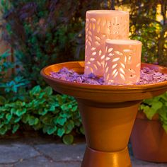 Terra-cotta pots and saucers are stacked and secured to create a decorative birdbath that doubles as a lantern stand.