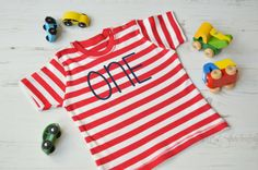 """This 1st birthday tshirt features a high quality vinyl """"one"""" in the colour of your choice, so your birthday boy or girl will look fantastic on their special day.   :: LISTING INCLUDES :: - Stripy short sleeved tshirt (your choice of 6-12mths, 12-18mths, 18-24mths) - Decorated with """"one"""" in a colour of your choice [Main Picture: Navy]  Features: • Thick 200gsm quality 100% cotton t-shirt • Stripy Short Sleeve t-shirt • High quality vinly which is CPSIA Certified • Made in the size of your…"""