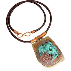 Turquoise Pendant Necklace A large turquoise nugget is woven and set into a copper setting and then cold connected to a nickel silver base. The pendant measures 1 3/4 x 2 1/2 inches. The necklace measures 21 inches with a leather cord and s-clasp closure. This is a one of a kind piece.