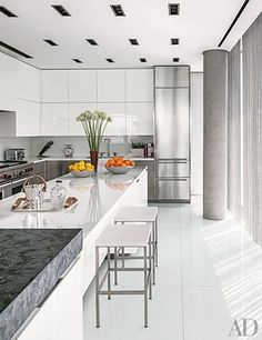 A West Village, Manhattan, kitchen in a sleek building by Richard Meier has glamorous shiny countertops of white crystallized glass. | archdigest.com