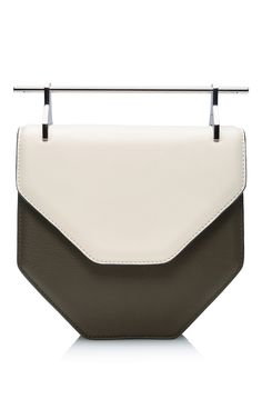 Featuring the M2Malletier's signature bold linear handle, this Pentagon bag delivers geometric intrigue in a sophisticated five-sided silhouette. Crafted from a complementing duo of ivory and forest green leathers, it also features an adjustable and removable leather strap, magnetic button closure, and interior pocket for practical luxury at its finest. Available now on Moda Operandi