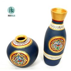 Terracotta Handpainted Warli Vase Set A Pair of beautifully handcrafted terracota vase set. In unique matki shape and tapered shape. Beautiful hand painting has been done around the neck of vases. Hand painted in a lovely blue with a patch of warli art in contrasting colours of gold and red. http://www.indikala.com/featured-products/terracotta-handpainted-warli-vase-set.html