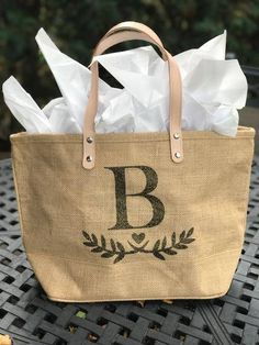 Jute/burlap Tote Bag makes a great gift. Mothers Day, bridesmaids, etc. Custom initials or monograms available. - Leather Handles - Zippered Closure - Size: 17.25W x 10.5H x 5.5 Gusset Made of Eco-friendly Jute/ Burlap in natural color, it gives a soft touch, but strong and durable gift