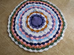 Old Fashioned Look Original Design Round Rug of Many Colors that is 31 inches. Made of acrylic yarn using three strands and lots of colors.