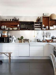 cocina blanca con cajas de madera que hacen de estantes