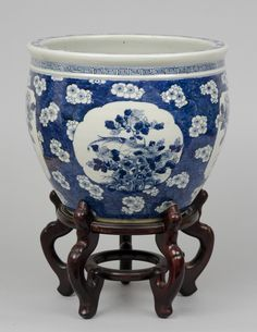 """Chinese porcelain blue and white jardiniere on stand decorated with prunus blossoms on an crackled ice ground with four shaped panels, each depicting different types of flowers.      China Circa 1880     Height: 18"""" 