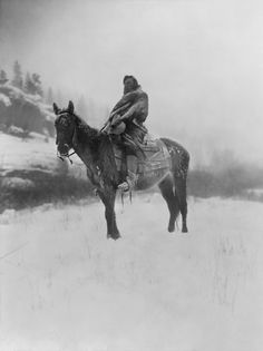 An Apsaroke (Crow tribe) man on horseback on snow-covered ground, probably in Pryor Mountains, Montana. Photographed by Edward Sheriff Curtis ca. 1908 (LOC)
