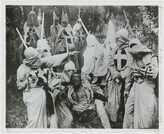 "Group of Klansmen surround freedman Gus (played by white actor Walter Long in blackface) in a scene from director D. W. Griffith's 1915 motion picture ""The Birth of a Nation."""