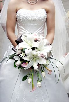 Make an entrance with a cascading bouquet of Oriental white lilies, roses and blush calla lilies.