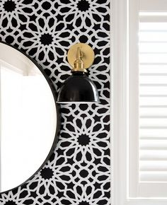 Black and white bathroom with black and gold wall sconces
