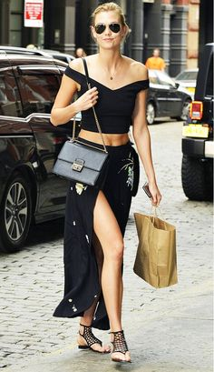 Karlie Kloss is wearing a black off the shoulder crop top, slit maxi skirt, cutout sandals, and a black bag by Dolce & Gabbana.